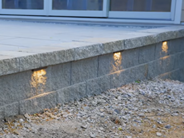 Crafted Workshop - Finished raised patio with CornerStone Retaining Wall and Under Cap Lighting